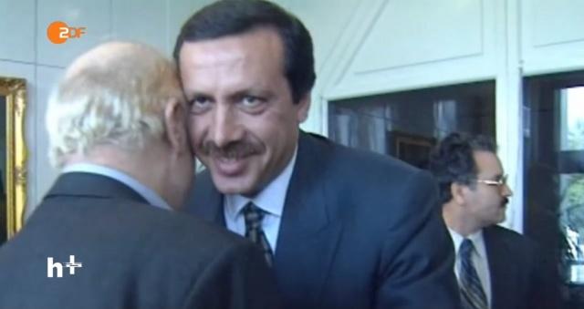 """AKP Ankara Milletvekili Yalçın Akdoğan'ın, CHP lideri Kemal Kılıçdaroğlu'nun Cemaatçilerle toplantı yaptığına ilişkin yayımladığı fotoğrafa cevap niteliğinde bir fotoğraf da Alman İkinci Devlet Kanalı ZDF arşivinden çıktı. Şimdi Yalçın Akdoğan'ın bu fotoğrafa vereceği cevap bekleniyor. Bakalım ne diyecek? Soru, zor: Cumhurbaşkanı Recep Tayyip Erdoğan kimi öpüyor? Şimdiye kadar Türk medyasında görülmemiş olan bu karelerde Cumhurbaşkanı Recep Tayyip Erdoğan'ın ak saçlı birini öptüğü görülmekte. İlerleyen saniyelerde bu kişinin FETÖ terör örgütü başkanı sıfatıyla Amerika Birleşik Devletleri'nden iade edilmesi istenen Fethullah Gülen olduğu anlaşılıyor. Cumhurbaşkanı Recep Tayyip Erdoğan'ın İstanbul Büyükşehir Belediye Başkanı olduğu dönemde çekilmiş olduğu zannedilen bu karelerde Fethullah Gülen'i """"sağlı sollu öptüğü"""" görülüyor."""